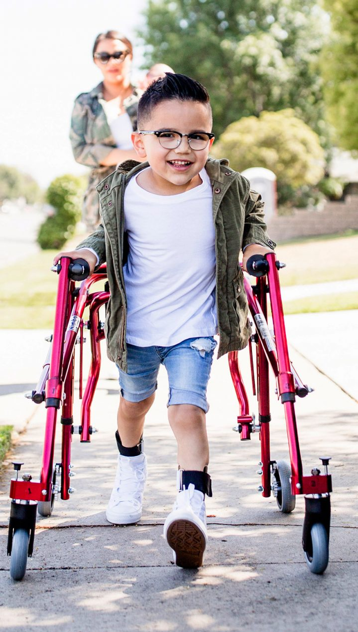 Boy with red pediatric walker