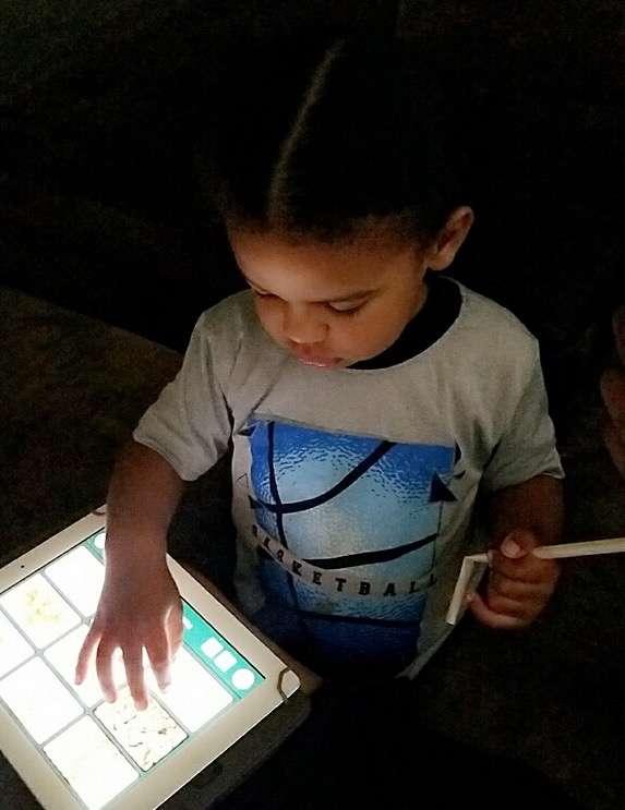 Little boy using an ipad to communicate