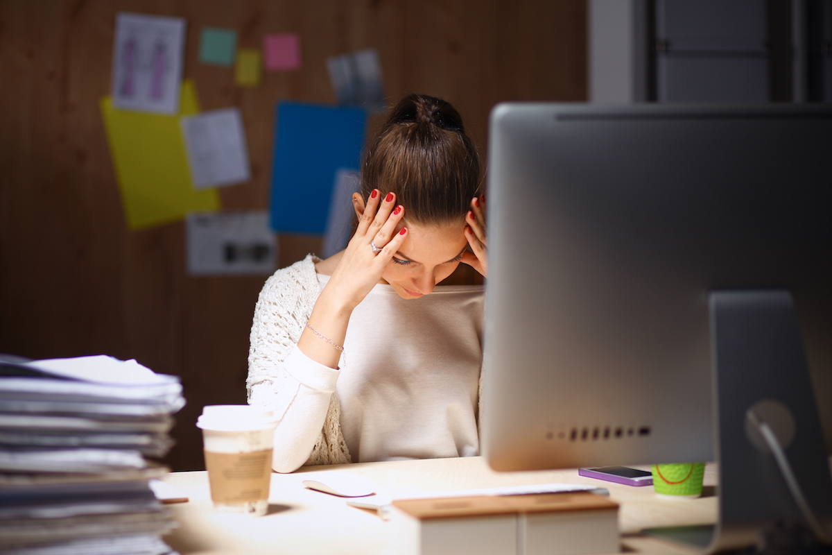Woman holding her head on a desk with stacks of papers