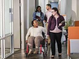 Woman in wheelchair talking to fellow employees