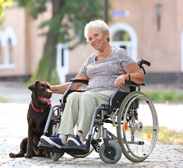 Woman in wheelchair with dog by her side